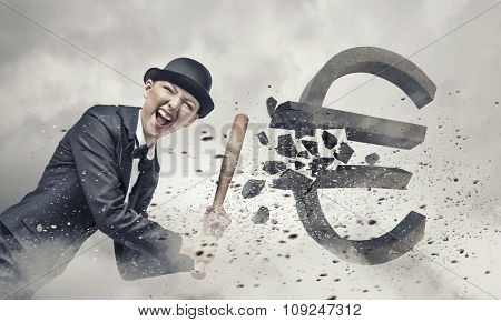 Young pretty woman in suit and hat crashing euro sign with baseball bat