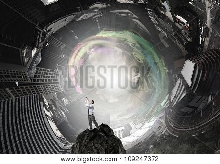 Young businessman on rock top playing pipe