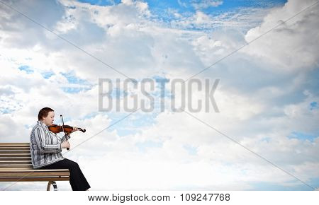 Middle aged stout woman sitting on bench and playing violin