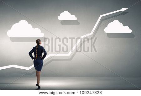 Back view of confident businesswoman with arms on waist