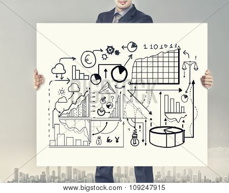 Businessman holding banner with business plan and strategy sketches