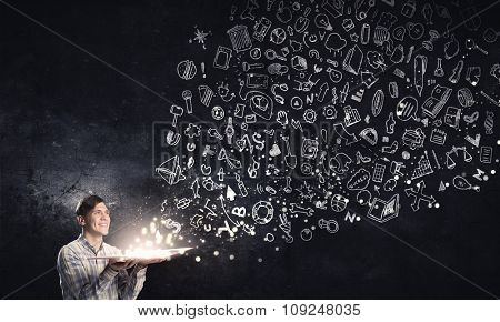 Young man with book in hands and characters flying out