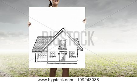 Unrecognizable woman holding placard with house symbol