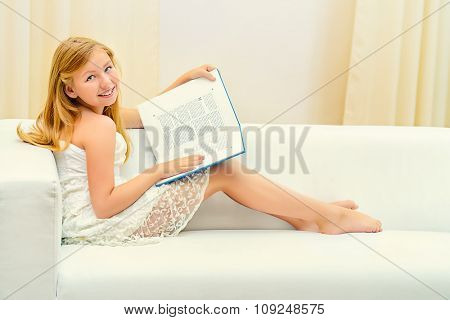 Teen girl sitting on a couch at home and reading a book. Education.