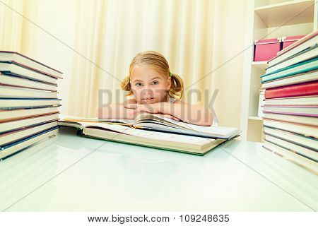 Five year old girl sitting at table at home with piles of books and smiles. Educational concept.