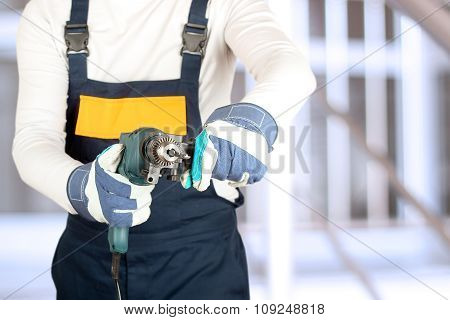 Caucasian Manual Worker  Standing With Drill