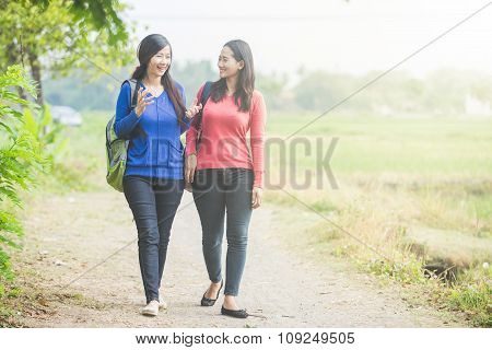 Two Young Asian Students Chatting While Walking Together