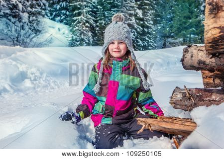 Kid sitting in snow with the wood in the background