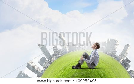 Young smiling businessman sitting on green grass planet