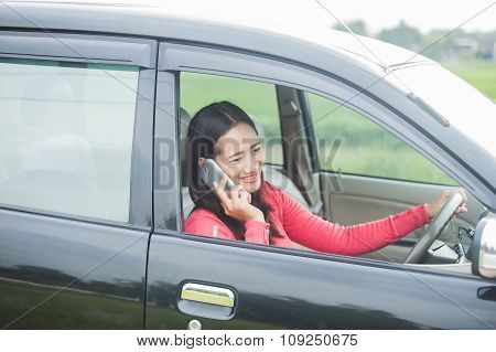 Young Asian Woman Talking On The Phone While Driving A Car