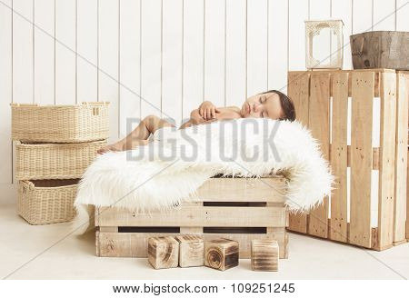 Adorable Toddler Sleeping On Box With Fur Blanket