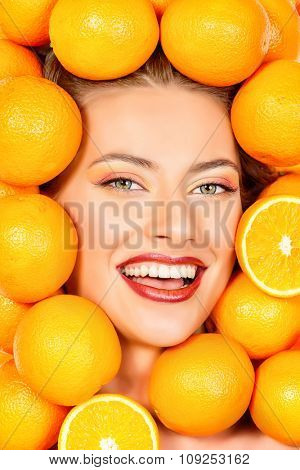 Close-up portrait of a beautiful smiling woman among fresh oranges. Healthy eating, juice. Make-up, cosmetics. Healthy teeth.