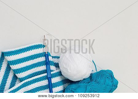 White and blue cotton yarn and crochet hook