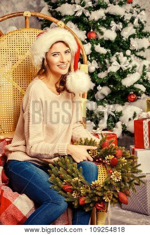 Happy beautiful young woman celebrating Christmas at home. Merry Christmas.