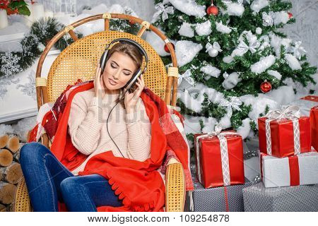 Beautiful girl enjoy listening to Christmas music at home.