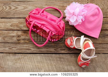 Child's pink shoes, hat and handbag on wooden background. Toned image.