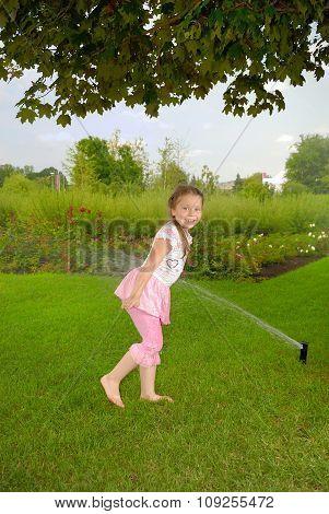 Little girl runs in park under water splashes