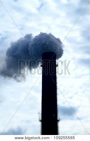 Toxic smoke from smokestack over clouds at the sky