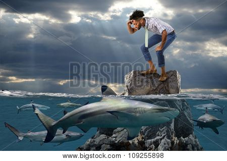 Young African American businessman standing on rock surrounded by sharks