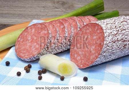 Salami and vegetables on wooden table
