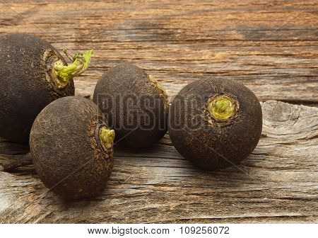 Black radish on wooden background