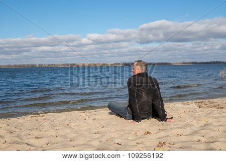 Hiker Man Sitting On The Beach, Back To Camera, Smiling, Relaxing And Enjoying Life