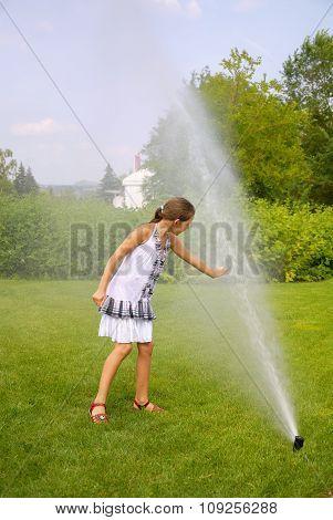 Little girl in park under water splashes