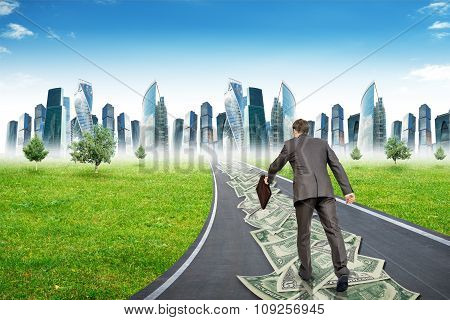 Businessman with suitcase on money road