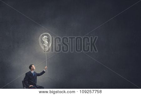 Businessman in chair holding dollar sign balloon