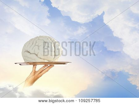 Hand holding metal tray with human brain symbol