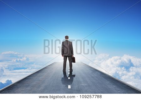 Businessman with suitcase on road in sky