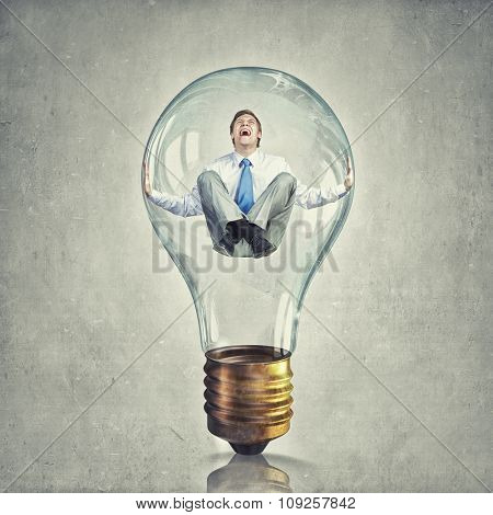 Young businessman trapped inside of light bulb and calling for help