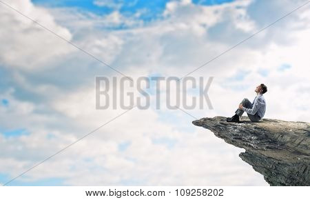 Young businessman sitting alone on rock top