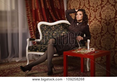 Woman In A Black Dress Sitting Ion The Couch