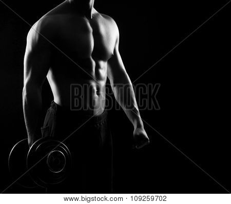 Strong, fit and sporty bodybuilder man with a dumbbell in monochromatic.