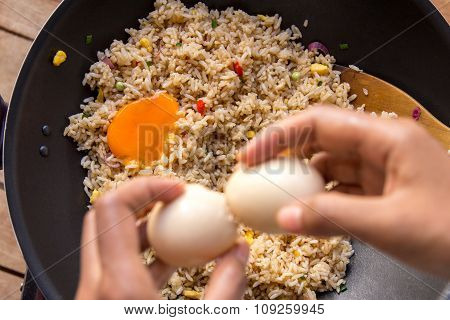 Human Hands Cracking Egg For Adding Into Fried Rice