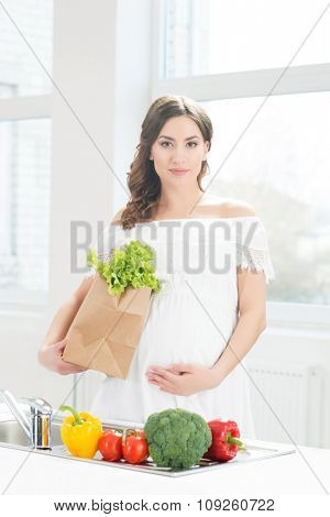 Beautiful pregnant woman with a shopping bag in the kitchen.