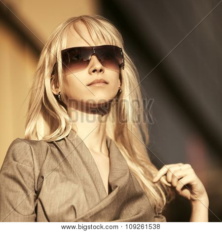 Blond fashion woman in sunglasses on city street