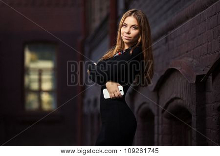 Young fashion woman in black dress with smart phone outdoor