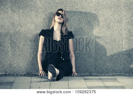 Sad young fashion blond woman in sunglasses sitting at the wall
