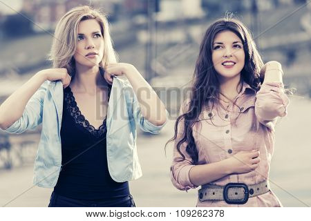 Two happy young fashion women walking on city street