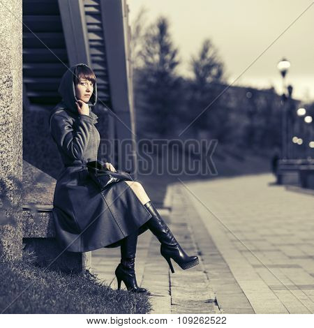 Sad young fashion woman in classic coat sitting at the wall
