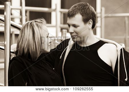 Happy young fashion couple talking on city street