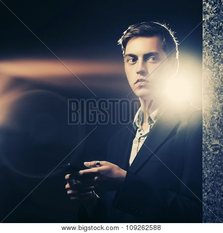 Young handsome man with a smart phone standing at the wall