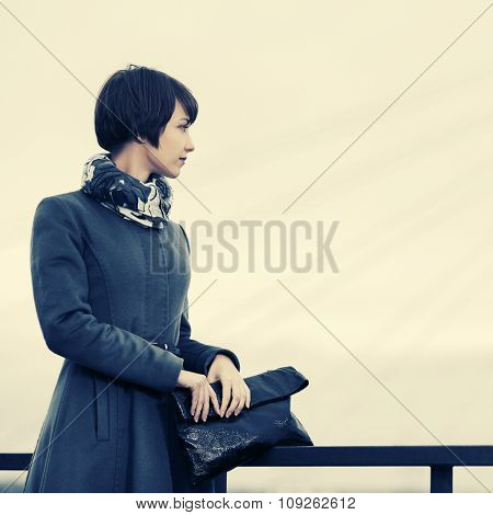 Sad young fashion woman in grey classic coat with handbag outdoor