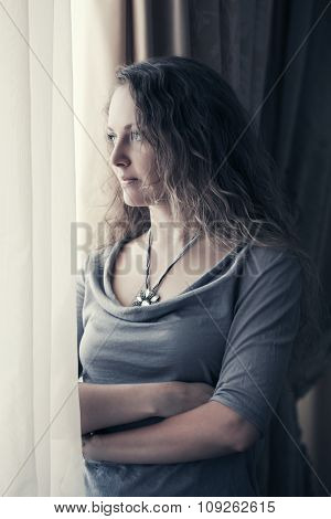 Sad beautiful woman looking out window