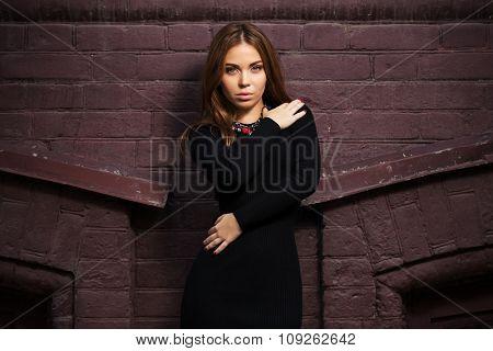 Sad young fashion woman in black dress at the brick wall