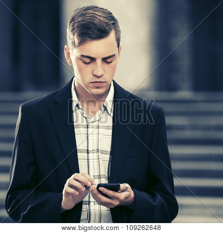 Young handsome business man using smart phone on city street