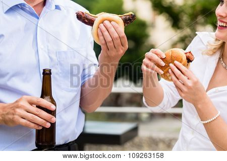 Colleagues having sausages and beer after work