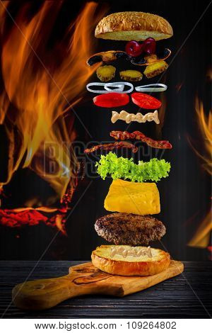 Hamburger stacked high with a juicy beef patty with flying ingredients - flames in the background